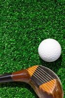 golfboll och förare på grönt gräs foto