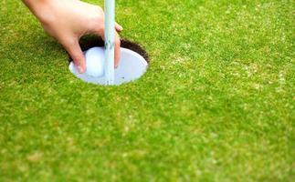 spelarhand som tar bort golfbollen från koppen efter skott foto