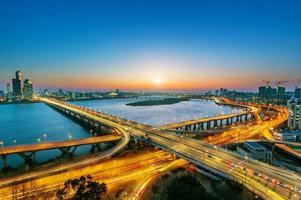 Seoul Mapo Bridge vid solnedgången med bilar och lätta spår foto
