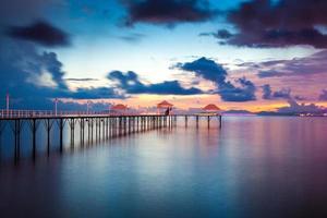 solnedgång brygga längs kusten foto