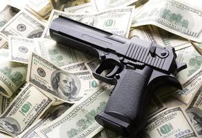 hög med pengar och pistol foto