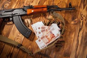 kalashnikov gevär och ryska rubel foto