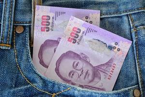 500 thailändska sedlar i mäns blå jeansficka foto