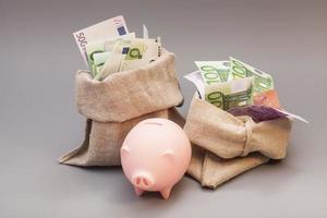 två pengar påse med euro och rosa spargris foto