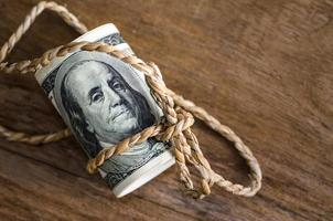 hundra dollar räkningar rullas upp med rep foto