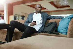 ung affärsman som väntar i hotellets lobby foto