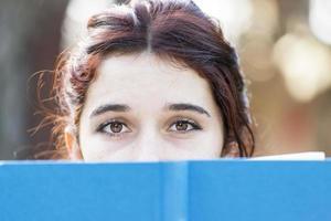 närbild porträtt av vacker kaukasisk kvinna med blå bok. foto