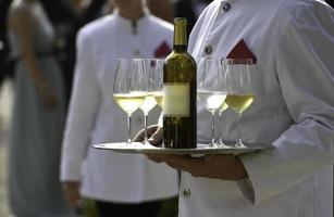 servitörer serverar vinrankor vid ett utomhusfest för bröllop foto