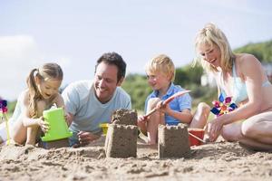 familj på stranden som gör sandslott