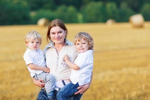 ung mamma och två små tvillingar pojkar som har kul foto