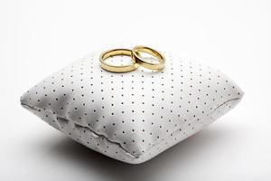 gyllene vigselringar på liten kudde foto
