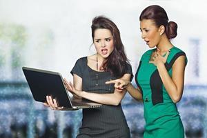två affärskvinnor som håller en bärbar dator och ser skockade ut foto