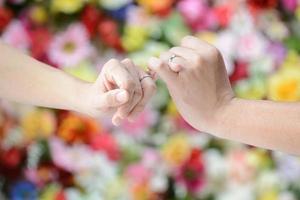 koppla lilla fingrar med någon för att bekräfta löfte foto