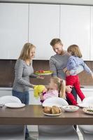 lycklig familj med barn som äter måltid i inhemskt kök foto