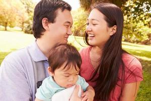 familj med baby i bärare som går genom parken foto
