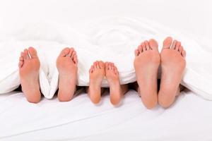 lycklig familj med tre som ligger under täcke foto