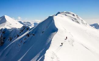 två vandrare på en vass, snöig bergskam. foto