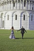 bruden och brudgummen går efter bröllopsceremonin i Pisa foto