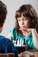 flicka och pojke som spelar schack foto