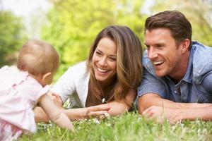 föräldrar med baby flicka sitter i fältet med sommarblommor foto