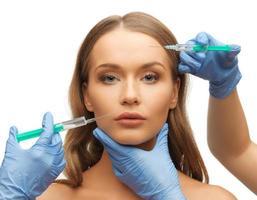 kvinna ansikte och kosmetolog händer foto