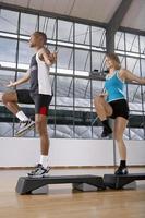 man och kvinna gör steg-aerobics. foto