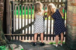 två blonda nyfikna flickor foto