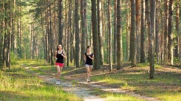 två kvinnor som joggar i skogen foto