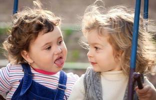 systrar som leker på gungor foto