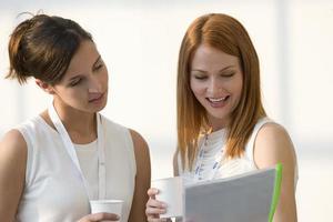 två affärskvinnor som granskar pappersarbete