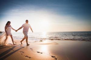 par för bröllopsresa gifte sig precis som springer på stranden foto
