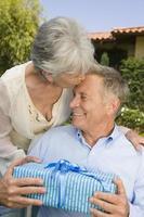 äldre kvinna som ger mannen födelsedagspresent foto