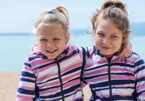 två små flickor syster till flickvännen vid havet foto