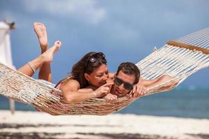 romantiska par som kopplar av i strandhängmatta foto