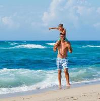 far och son som leker i havet