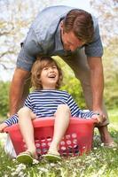 far som bär son som sitter i tvättkorg foto