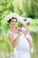 gravid mamma och hennes dotter har kul utomhus foto