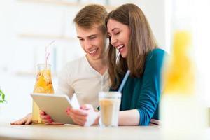 par som använder den digitala surfplattan på caféet foto