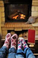 unga romantiska par kopplar av på soffan framför eldstaden foto
