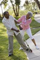 par som spelar på push-scooter i park foto