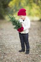 baby flicka i röda vantar och mössa som håller julgran foto