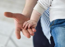far som ger hand till ett barn