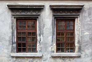 två fönster på en gammal grå stuckaturvägg.