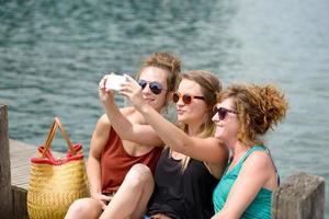 tre unga kvinnor på stranden med sin telefon foto