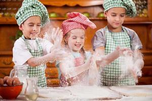 tre roliga små barn som skakar hand med mjöl i köket foto