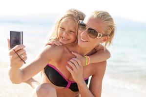mamma och dotter på stranden foto