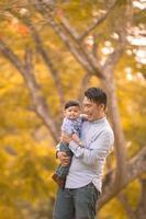 asiatiska far och son som har kul utomhus