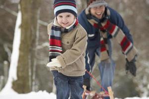 barn som drar släden genom vinterlandskapet foto