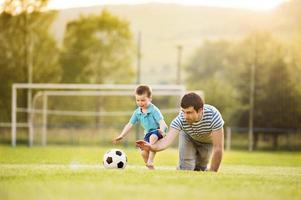 far och son spelar fotboll foto