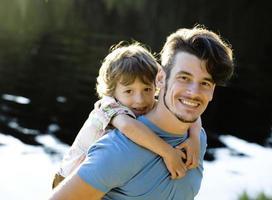 lilla söta son med leende far foto